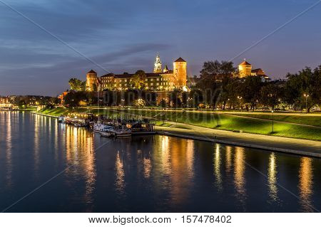 KRAKOW POLAND - 15TH OCTOBER 2016: A view of the outside of Wawel Royal Castle in Krakow at night from across the river Vistula