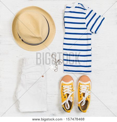 Child's striped t-shirt demin shorts accessories yellow shoes and straw hat isolated on white background. Top view. Flat lay. Kid's summer clothes collage