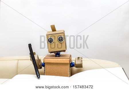 robot holds in his hands a pen pen and wrote in a notebook