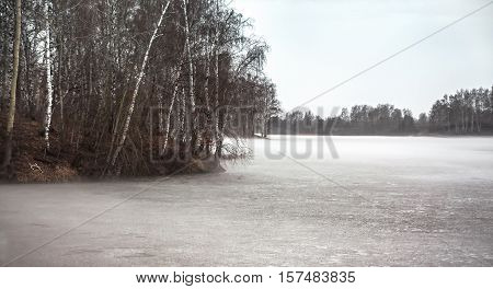 Gloomy landscape on frozen foggy lake with trees in season between winter and spring
