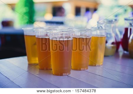 Beautiful vibrant picture of gold coloured beer glasses assortment, on wooden table, a summer sunny day, german unfiltered wheat beer