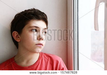 close up preteen boy portrait look at the window serious lonely sad expression