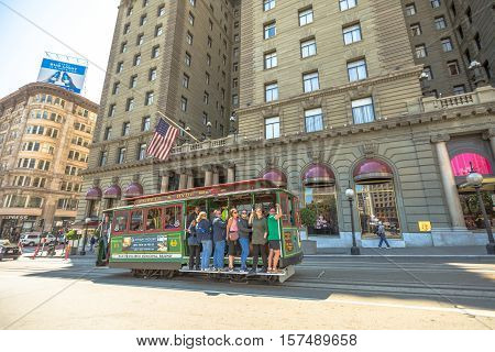 San Francisco, California, United States - August 17, 2016: The Cable Car of San Francisco full of tourists in front of luxurious Westin St. Francis hotel, along the famous Powell Street.
