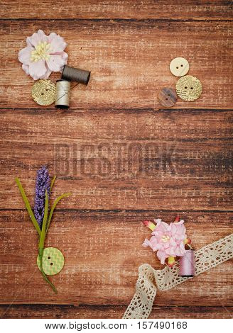 Piece of lace fabric with reels of thread, buttons and artificial lavander twig lying on wooden background. Scrapbooking materials. Copy space. Texture.