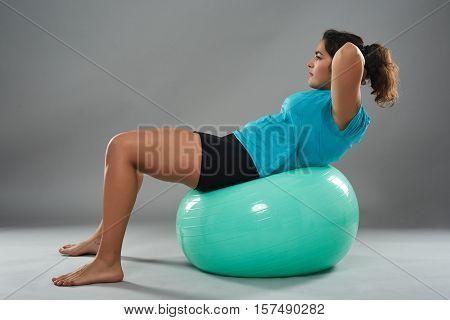 Latino Woman Doing Abs On Gym Ball