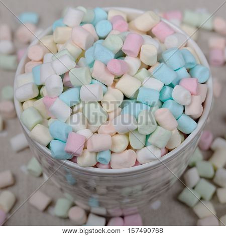 background or texture of pink, blu and white mini marshmallows, cup