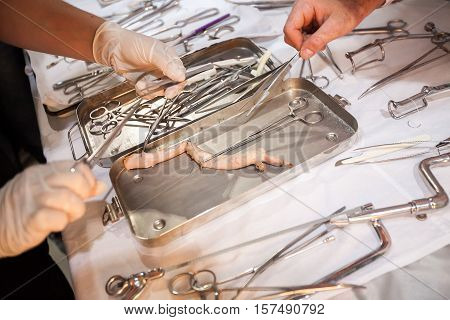 medical courses. surgical tool kit. surgeons sew up body. surgery close-up with surgeon cuts off the thread with scissors.