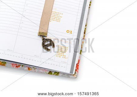 Notebook page fragment opened on first of January. Bookmark ribbon with horseshoe. Isolated on white. Copy space.