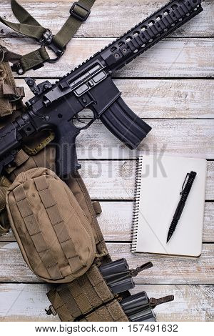 Assault riflepennotebook and military belt with ammo on table.Top view.Selective focus