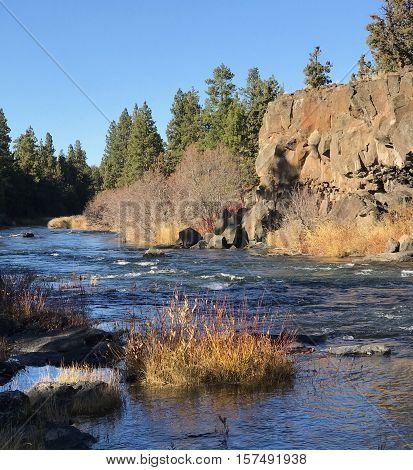 The Deschutes River flows through a canyon in Sawyer Park in Bend Oregon on a clear and sunny fall day.