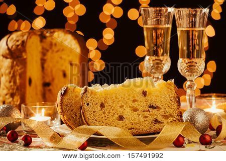 Sliced italian panettone and sparkling wine with decorations