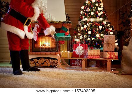 Santa Claus secretly leaves a gift under the Christmas tree