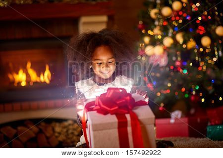 Happiness little girl interested looking in  magic Christmas present