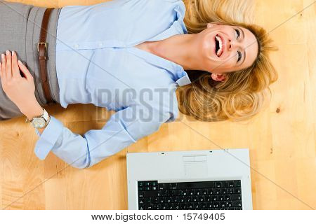 Businesswoman is lying on the floor at home relaxing, a laptop beside her