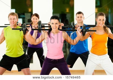 Group of five people exercising using barbells in gym or fitness club to gain strength and fitness