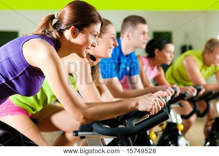 Group of five people in gym or fitness club exercising their legs doing cardio training poster