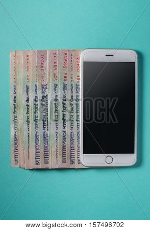 Row of Hundred rupee Indian currency notes laid along with a smartphone. Convenience of digital technology in banking.
