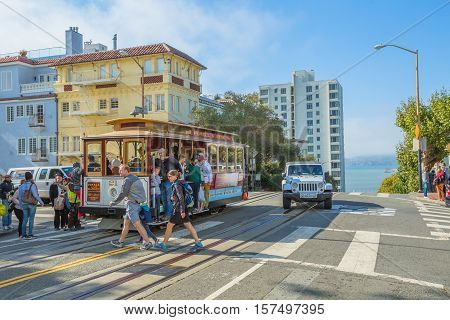 San Francisco, CA, USA - August 16, 2016: Cable Car of San Francisco, Powell-Hyde lines.Tourists crossing the intersection between Hyde and Lombard Street, one of the most crooked streets in the city.