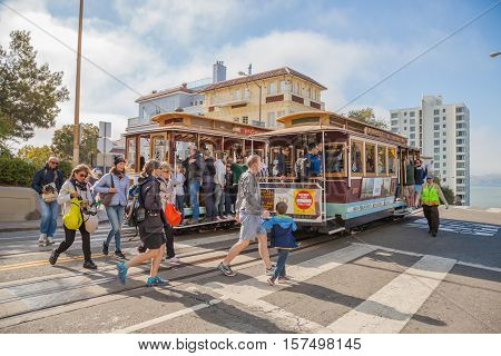 San Francisco, California, United States - August 16, 2016: two Cable Car tram, Powell-Hyde lines meet. Tourists crossing the intersection between Hyde and Lombard Street, popular touristic attraction