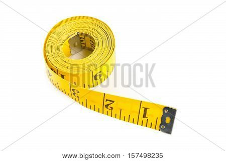 Coiled up yellow measurement tape over white background
