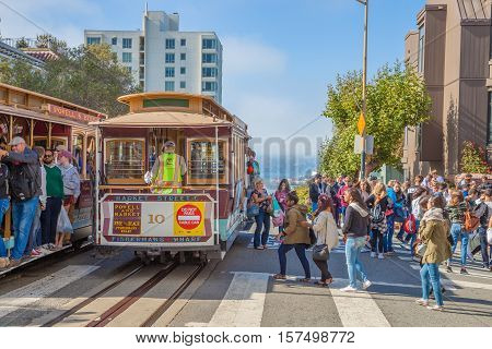 San Francisco, CA, United States - August 16, 2016: two Cable Car, Powell-Hyde lines meet. Crowds of tourists to the famous landmark of Lombard Street, one of the most crooked streets in the city.