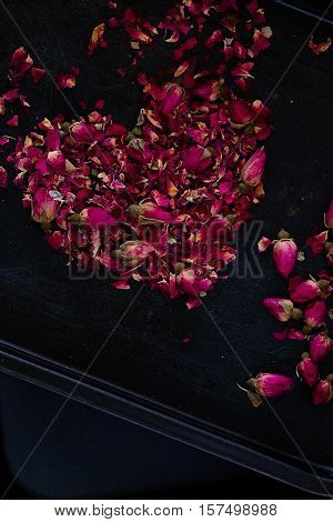 Dried rose petals and buds in a heart shape on a dark background. Romantic ingredient for tea bath or cosmetics. Copy space. Dark food photography
