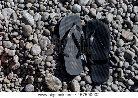 Beach shoes on pebble beach in afternoon