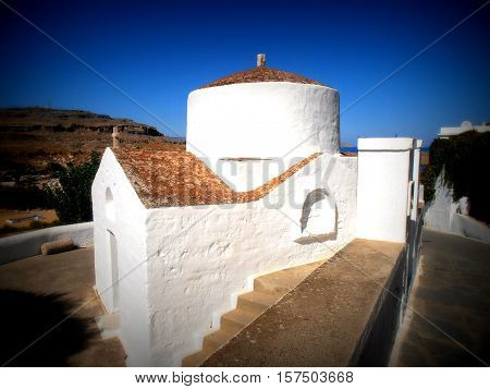 Church in the summer sunny day on the background blue sky. Rhodos.Greece.Lindos.