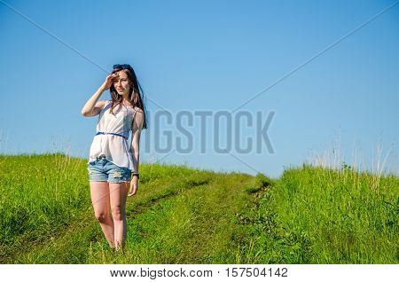 Brunette walks on a green meadow. the path is a beautiful girl .