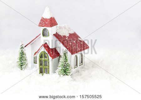horizontal Christmas image of a petite small little replica of a white church with a red roof with a complete white background.