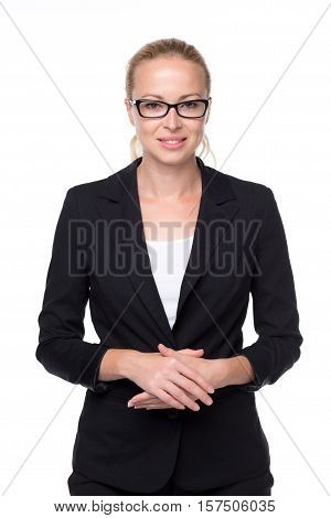 Portrait of beautiful young caucasian woman in business attire wearin black eyeglasses standing against gray background with arms cleanched .
