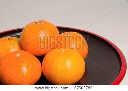 Mandarin oranges in Japan on red lacquer lacquerware
