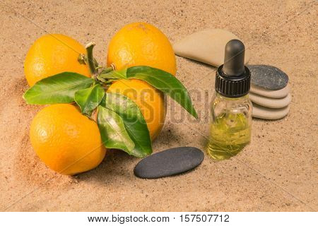 Bottle of citrus oil on the sand with tangerines and smooth stones
