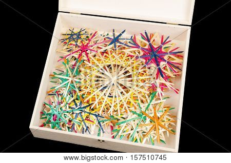 Straw stars in wooden box. Handmade colorful Christmas decoration for windows, as gifts or to hang on the xmas tree, traditionally made from natural straw. Photo from above on black background.