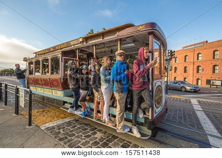 San Francisco, CA, United States - August 14, 2016: Cable Car Turntable or terminus, tourist attraction Powell-Hyde lines in Jefferson Street, Fishermen's Wharf. Passengers enjoy a ride in a cable car
