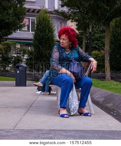 SANTANDER SPAIN - AUGUST 19: Elegant lady with red hair sitting on a bench looking to the left on August 19 2016