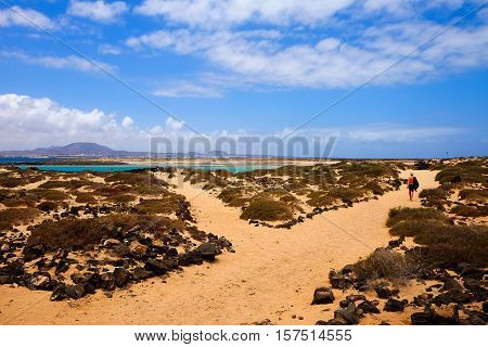 Beautiful landscape with unknown woman walking along a path closed to a beach. Location Canary island Lobos Fuerteventura Spain.