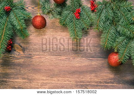 Christmas background with red balls berries and spruce branches