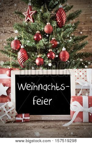 Chalkboard With German Text Weihnachtsfeier Means Christmas Party. Nostalgic Christmas Card For Seasons Greetings. Christmas Tree With Balls. Gifts Or Presents In The Front Of Wooden Background.