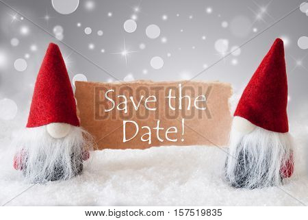 English Text Save The Date. Christmas Greeting Card With Two Red Gnomes. Sparkling Bokeh And Noble Silver Background With Snow.