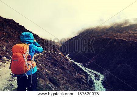 woman backpacker taking photo while trekking at the himalaya mountains