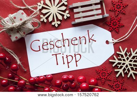 German Text Geschenk Tipp Means Gift Tip. Christmas Decoration Like Gift Or Present, Sleigh. Card For Seasons Greetings With Red Paper Background.