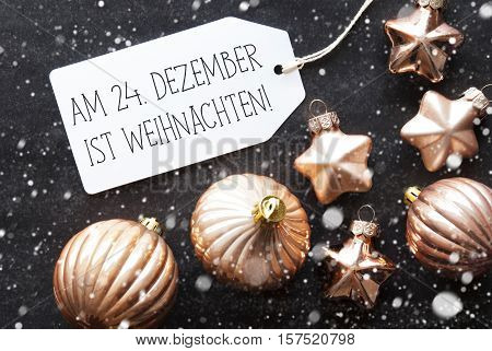 Label With German Text Am 24. Dezebmer Ist Weihnachten Means December 24th Is Christmas Eve. Bronze Christmas Tree Balls On Black Paper Background With Snowflakes. Flat Lay View