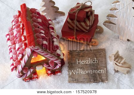 Label With German Text Herzlich Willkommen Means Welcome. Gingerbread House On Snow With Christmas Decoration Like Trees And Moose. Sleigh With Christmas Gifts Or Presents.