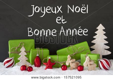 French Text Joyeux Noel Et Bonne Annee Means Merry Christmas And Happy New Year. Green Gifts With Christmas Decoration Like Tree, Moose Or Red Balls. Black Cement Wall As Background With Snow.