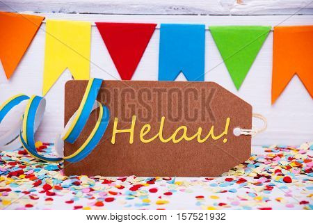 Brown Label With German Text Helau Means Happy Carnival. Party Decoration Like Streamer And Confetti. White Wooden Background. Greeting Card For Celebrations