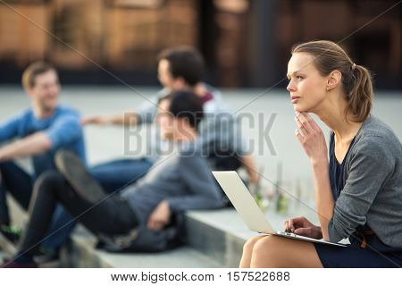 Portrait of a sleek young woman, using laptop computer, being pensive in urban/city context (shallow DOF; color toned image)