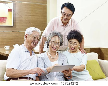 two active senior asian couples looking at tablet computer happy and smiling