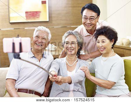 two active senior asian couples taking a selfie using mobile phone on a selfie stick happy and smiling