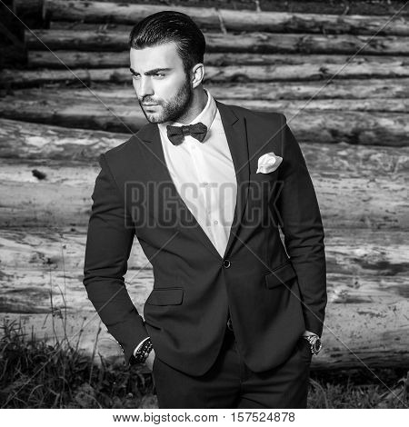 Black-white portrait of beautiful fashionable man in stylish suit against wooden background.